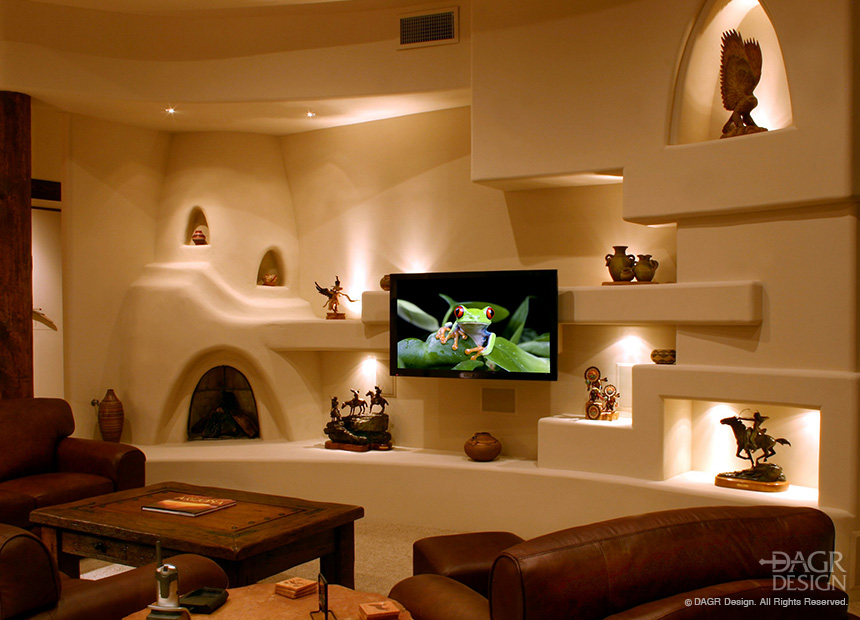 Southwestern kiva style custom drywall media wall incorporating custom shelves and lighted niches for art and collectibles along with a floating panel LCD TV mount and fireplace. Design and custom-build by DAGR Design