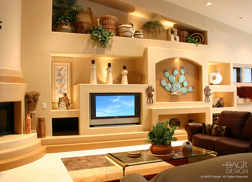 Custom drywall media wall with multiple custom arched niches, custom lighting effects, large screen tv, surround sound stereo system, and fireplace in a Southwestern style by DAGR Design