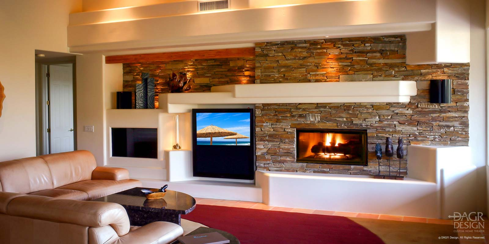 Custom drywall entertainment center with stacked stone walls, decorative lighted display shelves, and fireplace custom designed and installed by DAGR Design