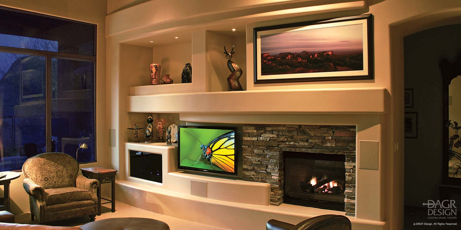 Custom home entertainment center fabricated in drywall with a curve design, stacked natural stone accents, lighted display niches, a floating panel LCD TV mount, and fireplace custom designed and installed by DAGR Design.