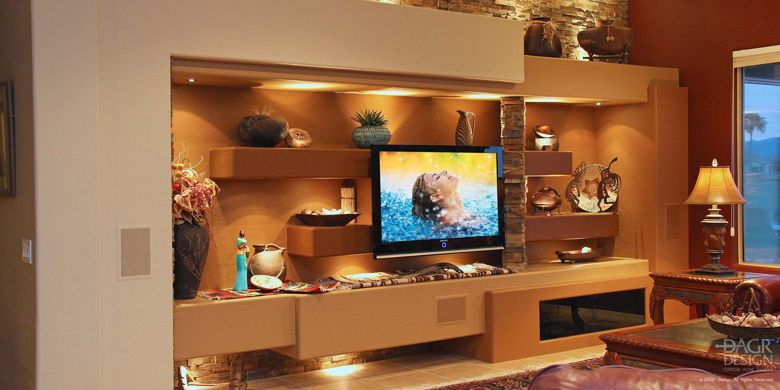 High end custom designed home media wall with floating panel LCD TV mount, natural stacked stone accents, custom shelving with accent lighting custom designed and installed by DAGR Design