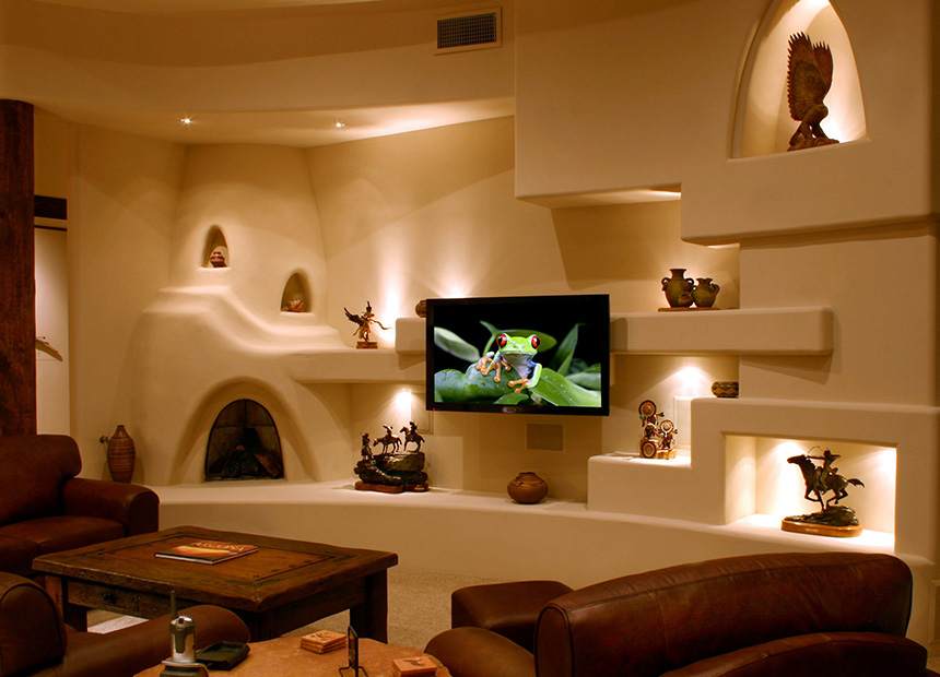 Custom media wall in round room with kiva style fireplace.